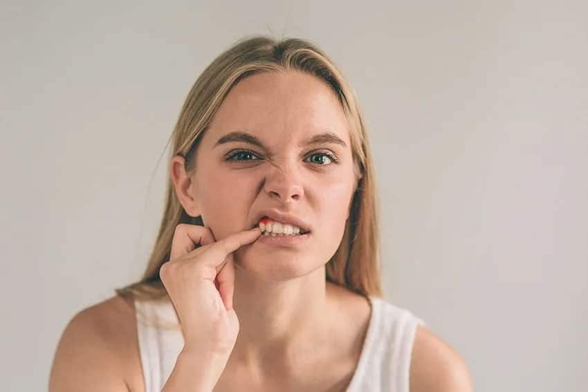 blonde woman picks at her teeth with her finger in front of a mirror
