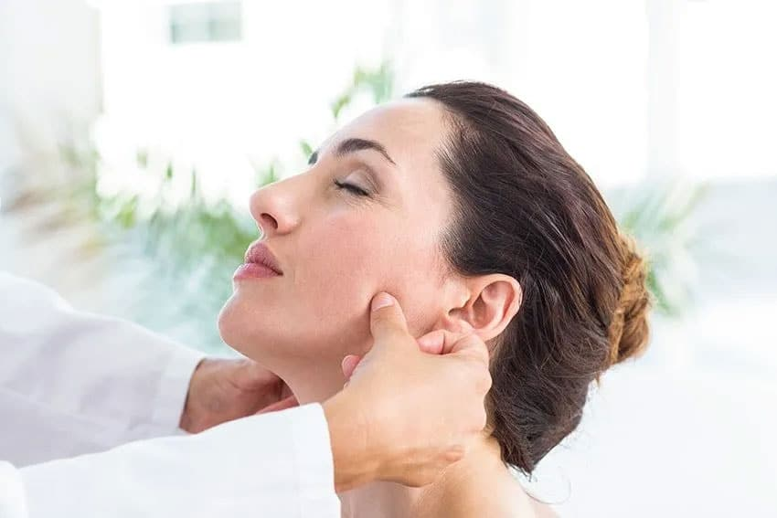 Doctor massaging a female patients jaw line