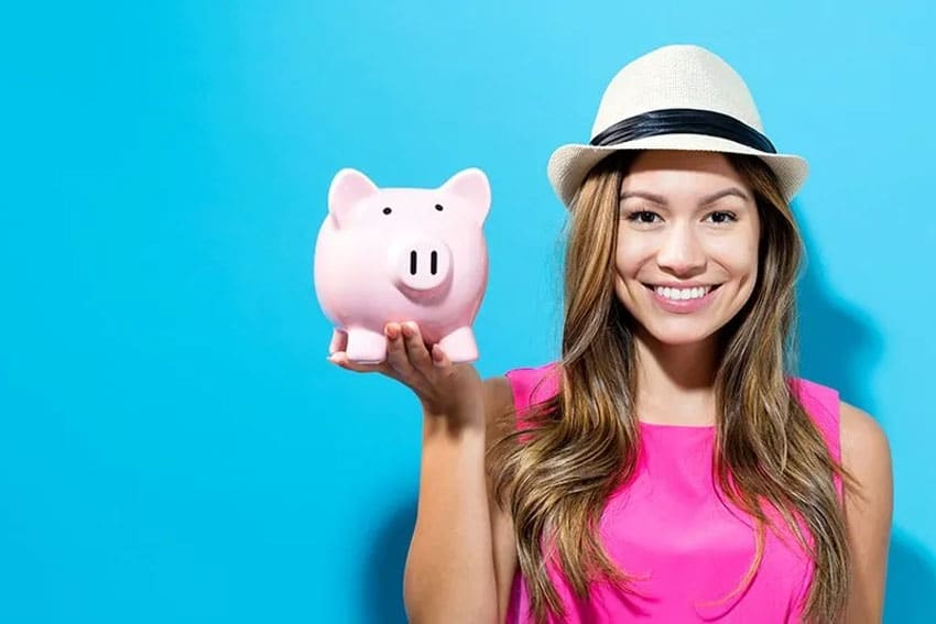 Trendy young woman with cute hat shows off her piggy bank - and smile
