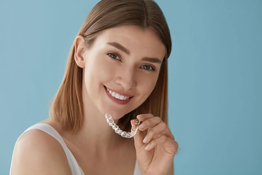 young woman prepares to put in Invisalign clear braces on her teeth