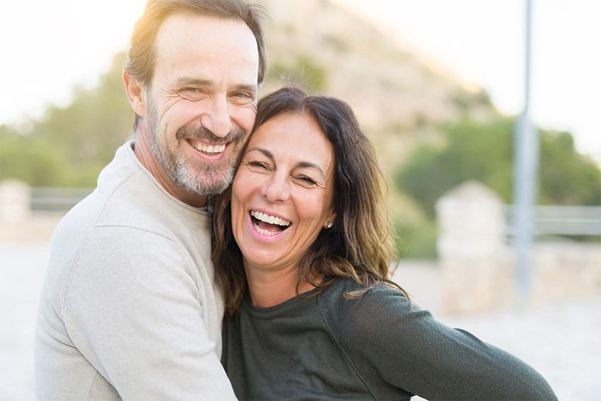 Mature couple laughs with one another while taking a walk