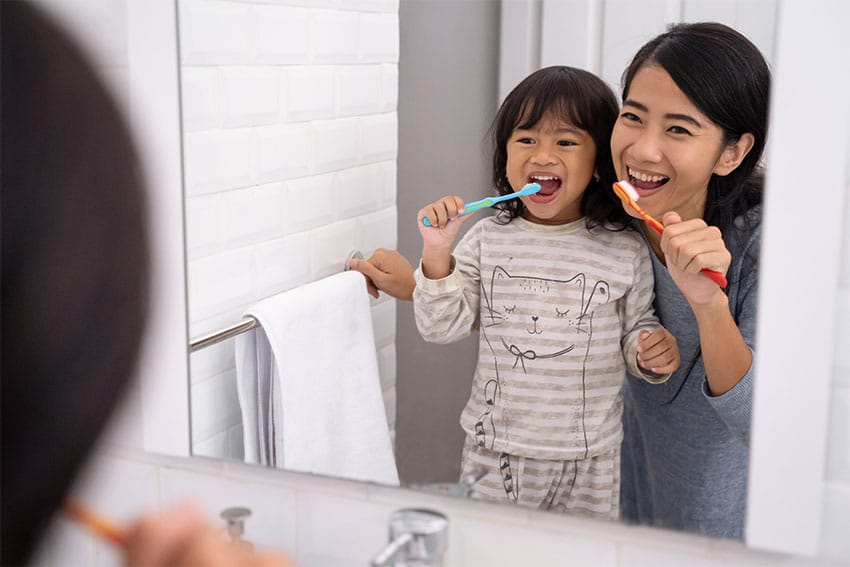 Mother and young daughter looking into the mirror while brushing their teeth