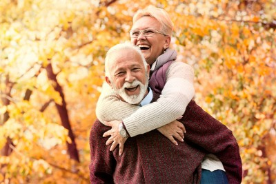 Older couple jokes around with one another in the park on a beautiful fall day