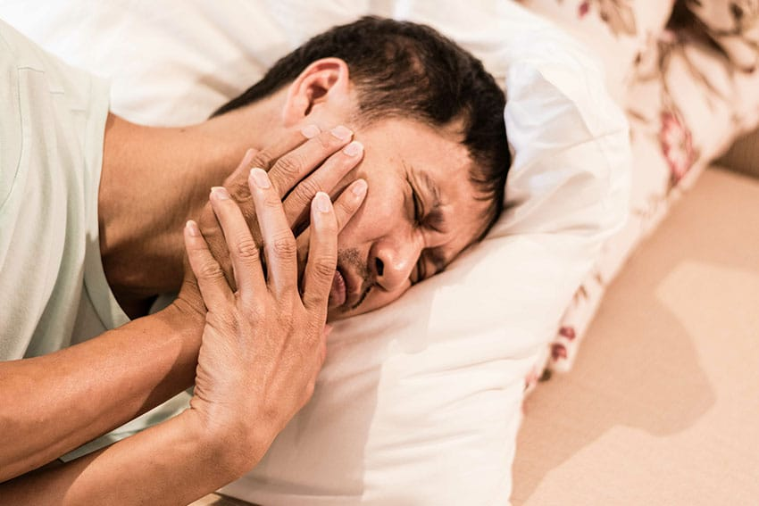 man lays on his side in bed, holding his jaw due to pain