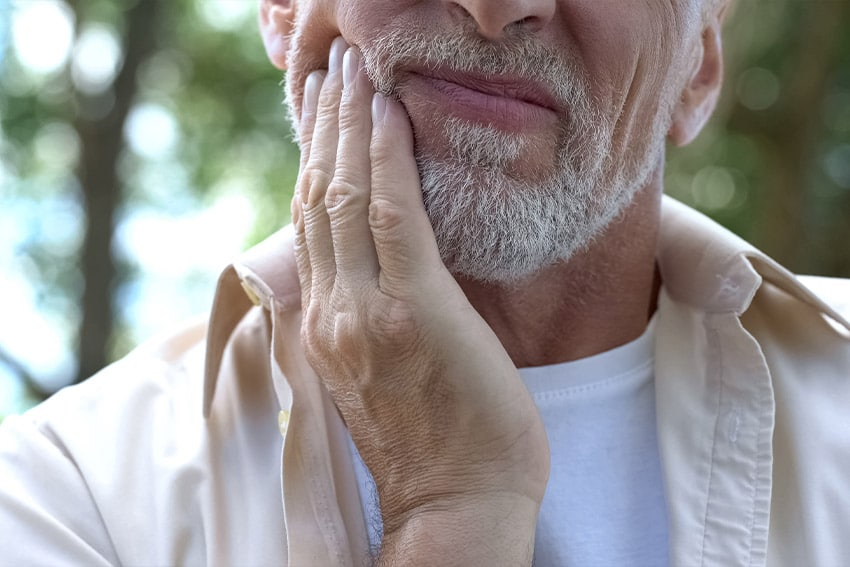 senior man rubbing his jaw due to pain