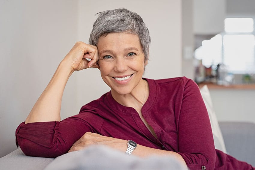 mature woman relaxing on her couch at home, smiling